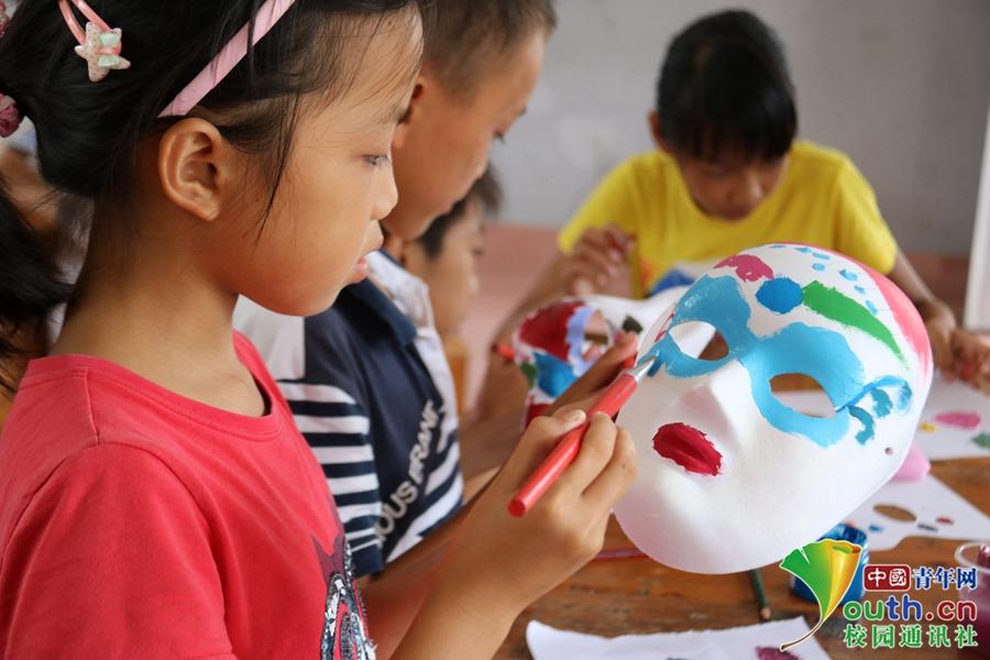 手绘面具课上小朋友拿起画笔沾满颜料在自己的国度